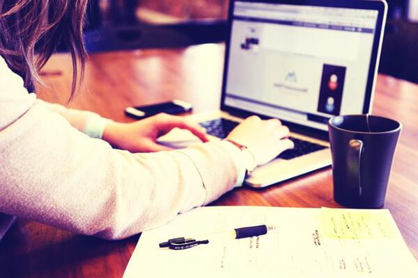 Chica estudiando y trabajando con ordenador sobre una mesa con movil y libreta